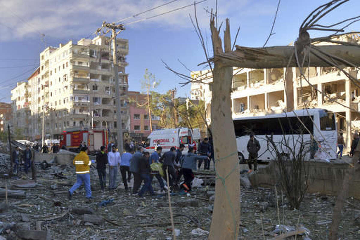 Locals help medics carry a wounded person after an explosion in the southeastern Turkish city of Diyarbakir, early Friday, Nov. 4, 2016. A large explosion hit Diyarbakir, the largest city in Turkey's mainly Kurdish southeast region on Friday, wounding several people the state-run Anadolu Agency reported. The cause of the explosion was not immediately known but local media said it may have been caused by a car bomb. (IHA via AP)