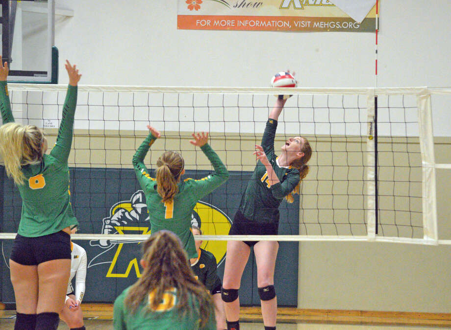 Metro-East Lutheran senior Courtney Fenelon goes for a kill over a pair of Piasa Southwestern players during Tuesday's match at MELHS.