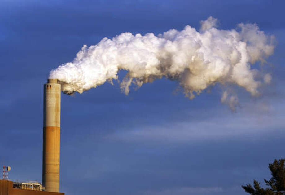 FILE - In this Jan. 20, 2015 file photo, steam billows from the chimney or a coal-fired Merrimack Station in Bow, N.H. USA. The Paris Agreement on climate change comes into force Friday Nov. 4, 2016, after a year of remarkable success in international efforts to slash man-made emissions of carbon dioxide and other global warming gases. (AP Photo/Jim Cole, FILE)