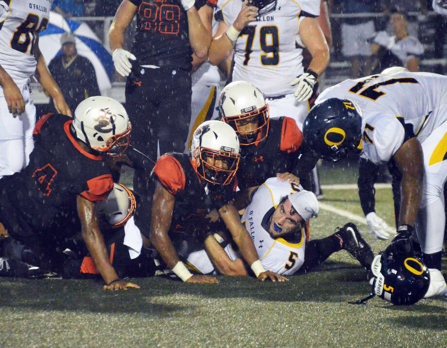 Members of the Edwardsville defense team up to tackle O'Fallon running back Mason Hewitt (No. 5) during the first quarter Friday at the District 7 Sports Complex.