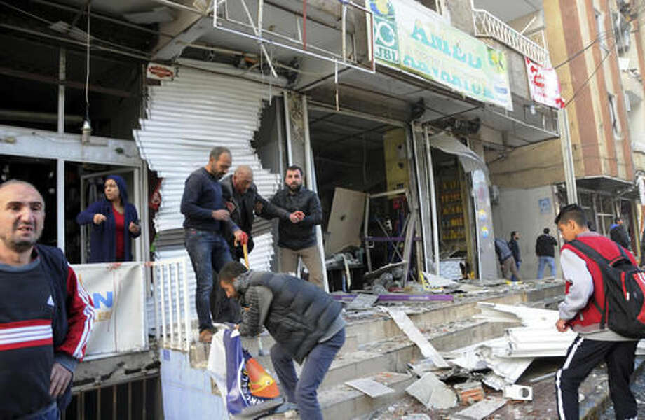 People help a wounded man after an explosion in southeastern Turkish city of Diyarbakir, early Friday, Nov. 4, 2016. A large explosion hit the largest city in Turkey's mainly Kurdish southeast region on Friday. The cause of the explosion was not immediately known but Hurriyet newspaper said it may have been caused by a car bomb.(IHA via AP)