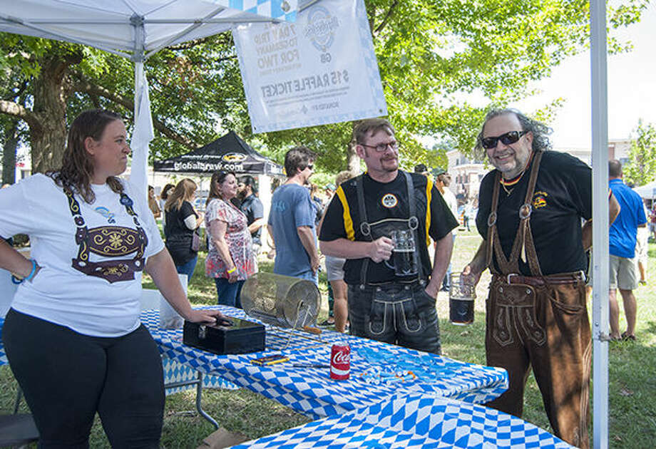 Two members of the band Uber Cool, clad in lederhosen, stop to chat at a booth.