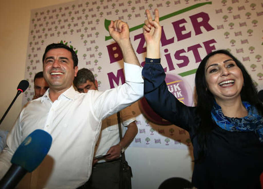 FILE-In this Sunday, June 7, 2015 file photo, Selahattin Demirtas, left, co-chair of the pro-Kurdish Peoples' Democratic Party, (HDP) and Figen Yuksekdag, the other co-chair celebrate following a news conference in Istanbul. regarding their party's success at the elections. Authorities in Turkey detained 11 pro-Kurdish lawmakers early Friday, Nov. 4, 2016 as part of ongoing terror-related investigations, including Demirtas, Yuksekdag and other senior officials, the Interior Ministry said. The government accuses the HDP of being the political arm of the outlawed Kurdistan Workers' Party, or PKK, which has fought an armed insurgency against the state for over three decades. The HDP rejects the accusation.(AP Photo/Lefteris Pitarakis, File)