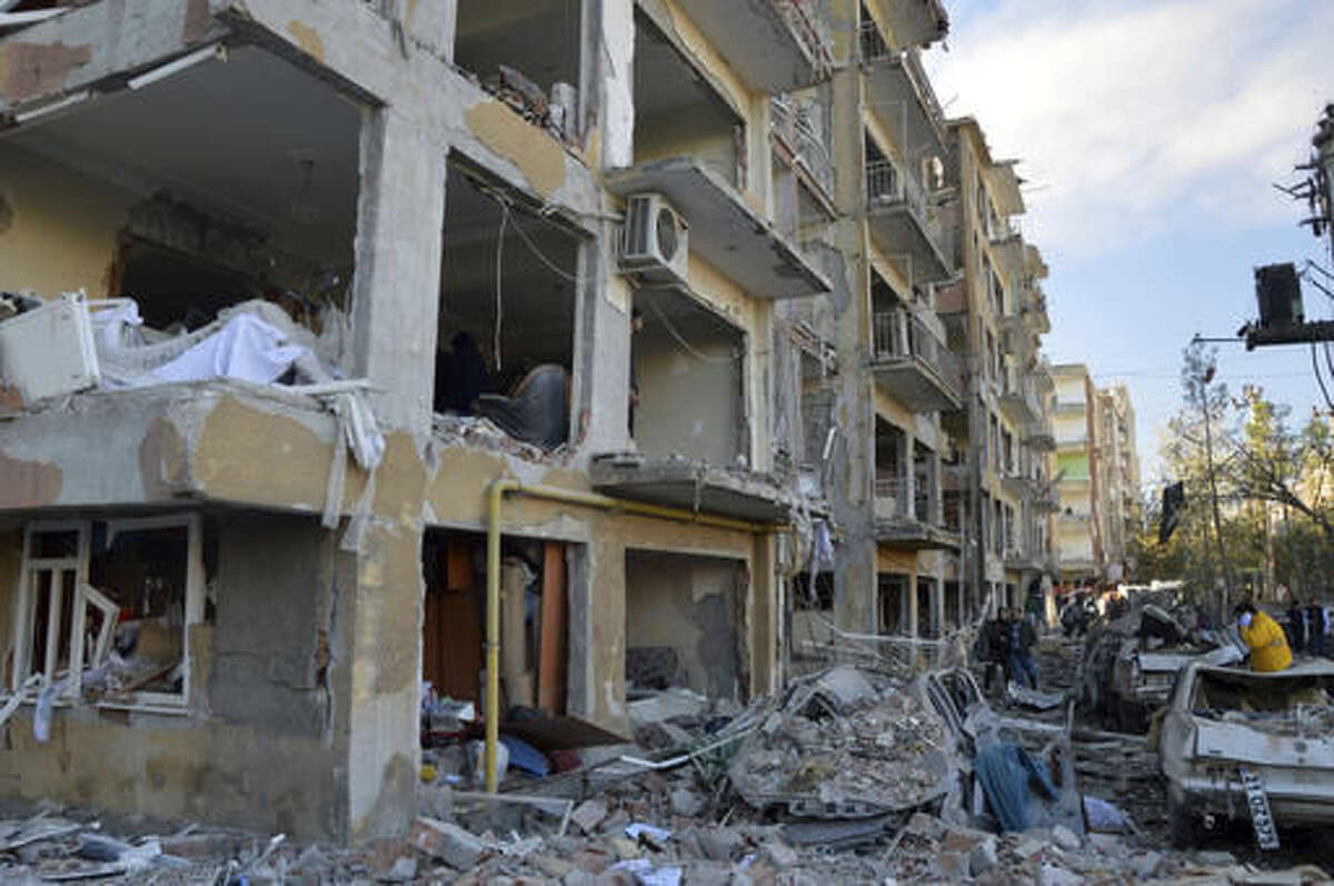 People view the damage after an explosion in the southeastern Turkish city of Diyarbakir, early Friday, Nov. 4, 2016. A large explosion hit Diyarbakir, the largest city in Turkey's mainly Kurdish southeast region on Friday, wounding several people the state-run Anadolu Agency reported. The cause of the explosion was not immediately known but Hurriyet newspaper said it may have been caused by a car bomb. (IHA via AP)