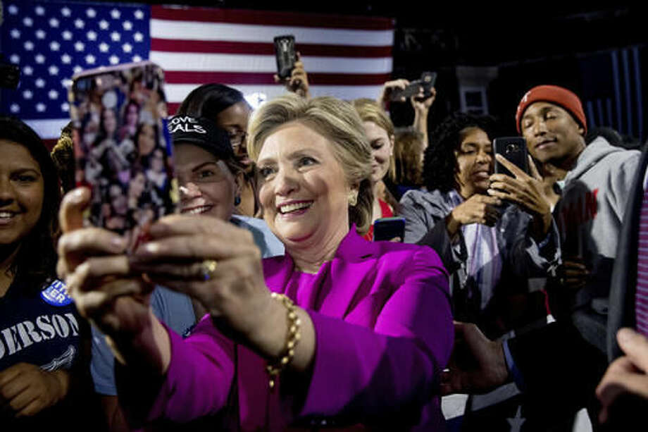 Democratic presidential candidate Hillary Clinton, left, and performer Pharrell Williams, right, greets members of the audience after speaking at a rally at Coastal Credit Union Music Park at Walnut Creek in Raleigh, N.C., Thursday, Nov. 3, 2016. (AP Photo/Andrew Harnik)