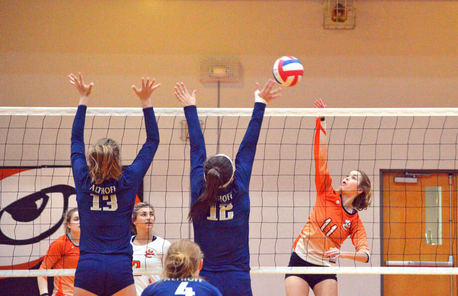 Edwardsville senior Shelby Saye tries to hit the ball over a pair of Althoff players during Tuesday's match at EHS.