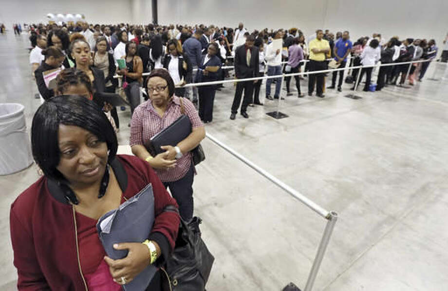 FILE - In this Wednesday, Oct. 19, 2016, file photo, Kanockwa Horton, left, from Stone Mountain, and Jacqueline Merritt, from Atlanta, stand first in line at the Airport Community Job Fair, in Atlanta, joined by hundreds of other applicants in line before the 10 a.m. opening. On Friday, Nov. 4, 2016, the Labor Department issues its jobs report for October. (Bob Andres/Atlanta Journal-Constitution via AP, File)