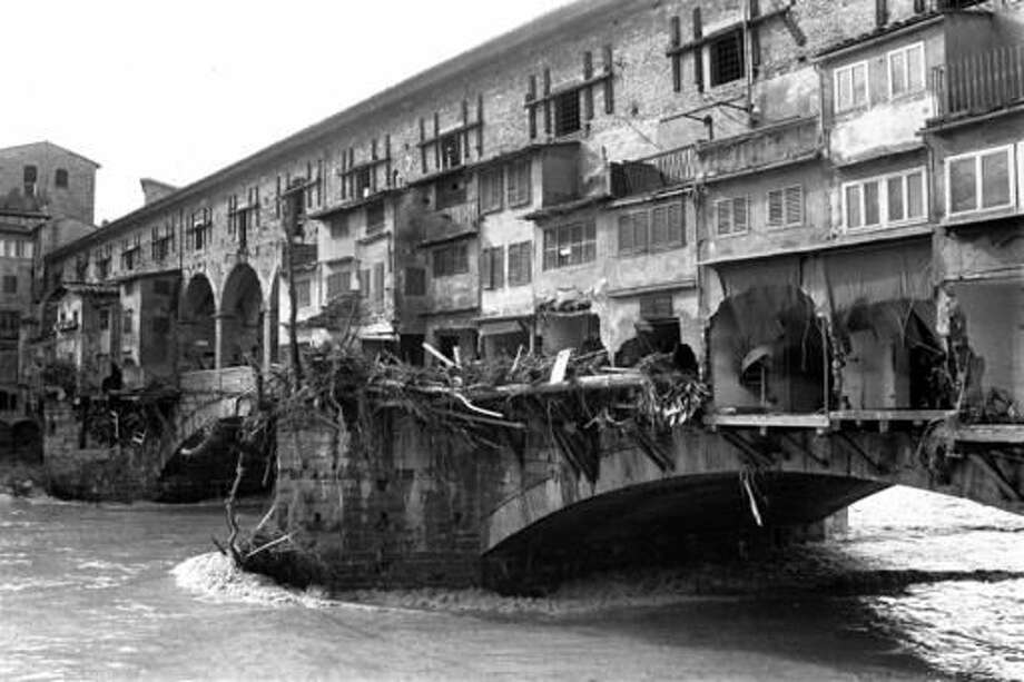 """FILE - This black and white Nov. 5, 1996 file photo shows the 14th century Ponte Vecchio (Old Bridge) after the banks of the River Arno overflowed and flooded the city. A Renaissance painting, Giorgio Vasari's """"The Last Supper"""", that was badly damaged in a 1966 flood in Florence, will be reinstalled in the Basilica of Santa Croce and unveiled to the public on Friday, Nov. 4, 2016 after years of painstaking restoration. (AP Photo, files)"""