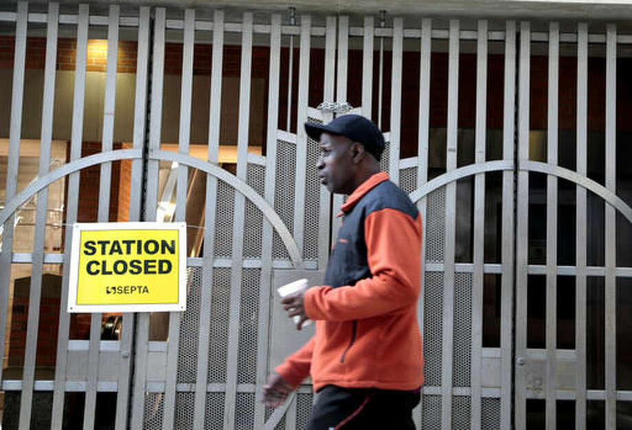 A pedestrian passes a locked rail station in west Philadelphia Tuesday Nov. 1, 2016. Commuters scrambled Tuesday to find alternate ways to travel as transit workers in Philadelphia hit the picket lines after the city's main transit agency and a union representing about 4,700 workers failed to reach a contract agreement. The union went on strike at 12:01 a.m. Tuesday, shutting down Southeastern Pennsylvania Transportation Authority buses, trolleys and subways that provide about 900,000 rides a day. (AP Photo/Jacqueline Larma)