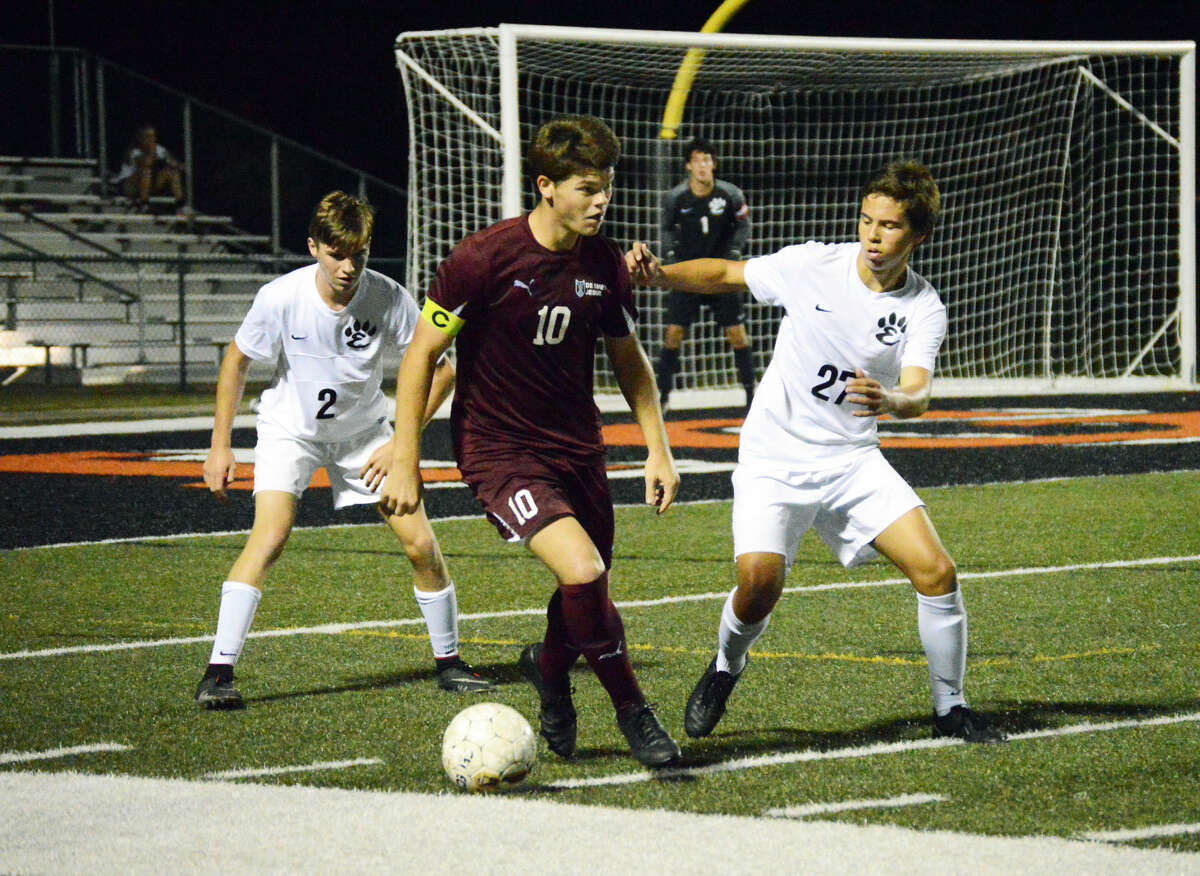 Edwardsville defenders Blake Conway, left, and Zach Timmermann, right, defend a De Smet player during the second half at the District 7 Sports Complex.