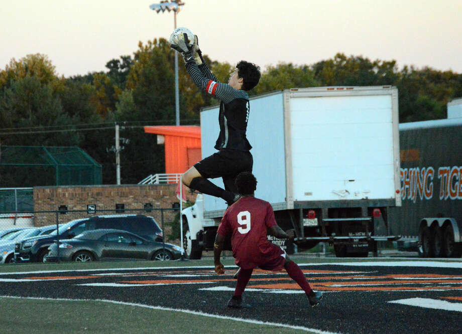Edwardsville keeper Dan Picchiotti leaps for a ball early in the first half.