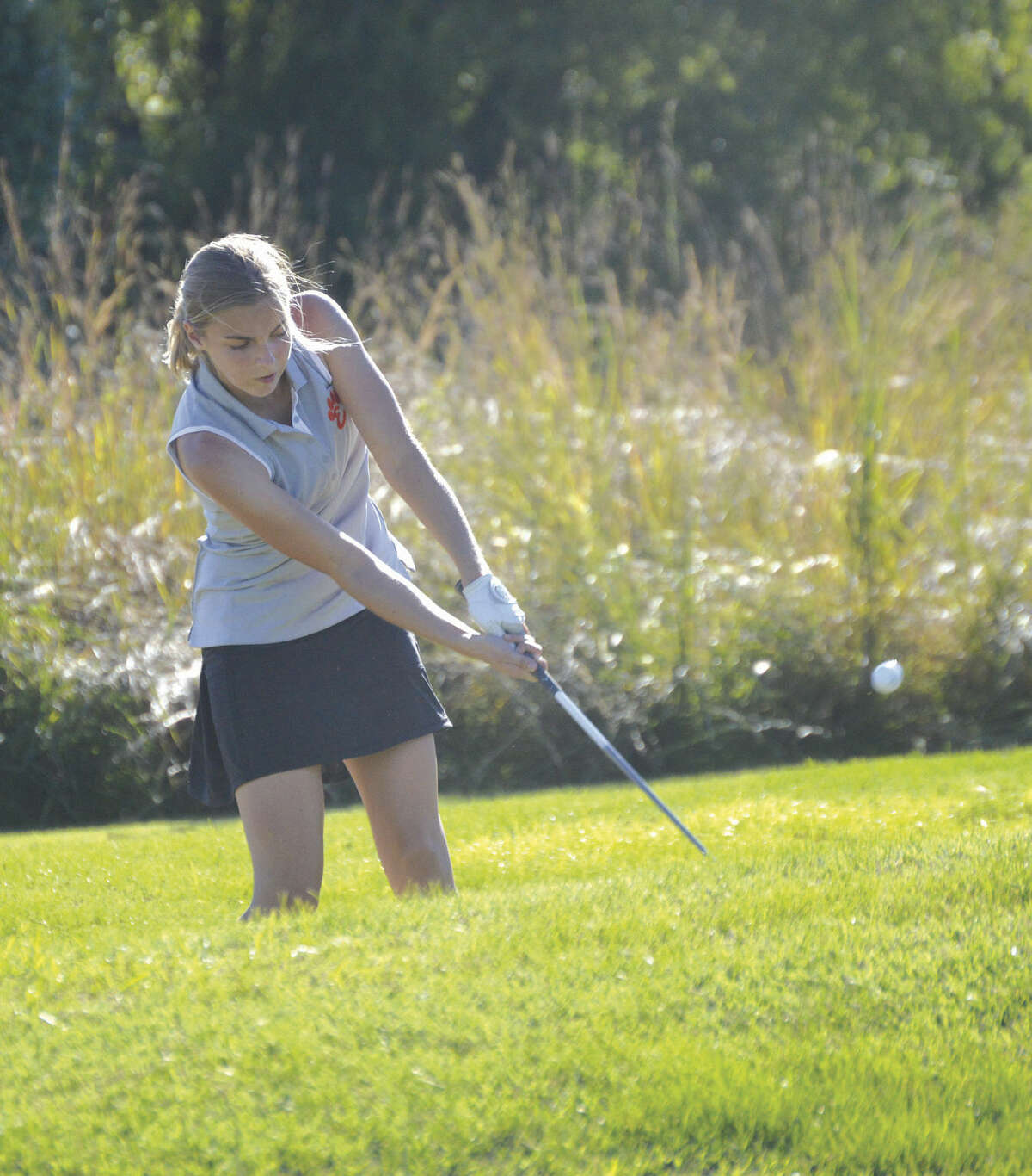 Edwardsville sophomore Meara Schaefer hits her shot out of the bunker and on to the green on hole No. 8 at Arlington Greens Golf Course.