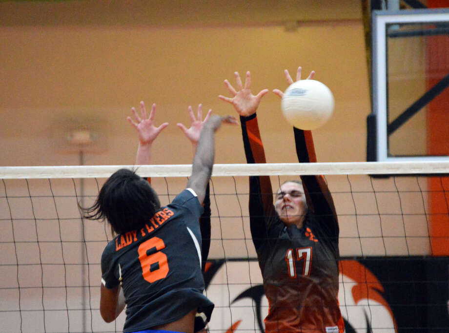 Edwardsville's Rachel Pranger, right, tries to block a kill attempt by an East St. Louis during the first game Thursday at Lucco-Jackson Gymnasium.