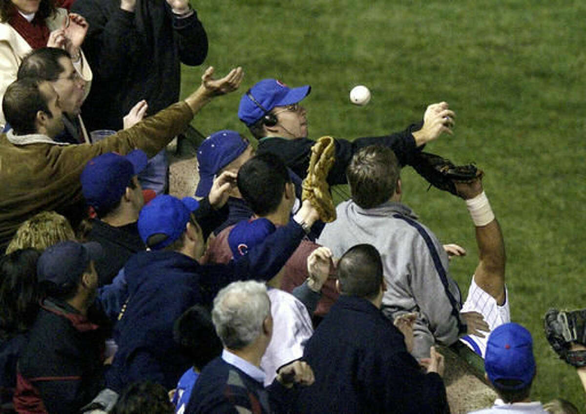 FILE - In this Oct 14, 2003, file photo, Steve Bartman catches a ball as Chicago Cubs left fielder Moises Alou's arm is seen reaching into the stands, at right, against the Florida Marlins in the eighth inning during Game 6 of the National League championship series Tuesday, Oct. 14, 2003, at Wrigley Field in Chicago. Bartman's spokesman, Frank Murtha, tells USA Today that Bartman is overjoyed by the Cubs first World Series title since 1908, but won't attend the victory parade in Chicago on Nov. 4, 2016. (AP Photo/Morry Gash, File)