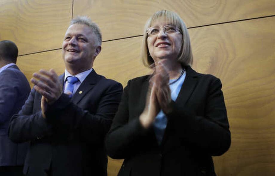 This photo taken on Thursday, Nov 3, 2016 shows Bulgaria's centre-right ruling GERB party presidential candidate Tsetska Tsacheva, right, and vice-president Plamen Manushev, left clap hands during their pre-election campaign in Pernik, Bulgaria . Bulgarians will to choose their new president on Sunday to replace incumbent Rosen Plevneliev after his five-year term ends next January. The election campaign focused mainly on the future of the European Union, relations with Russia and the threats from a possible rise in migrant inflows from neighboring Turkey. (AP Photo/Valentina Petrova)