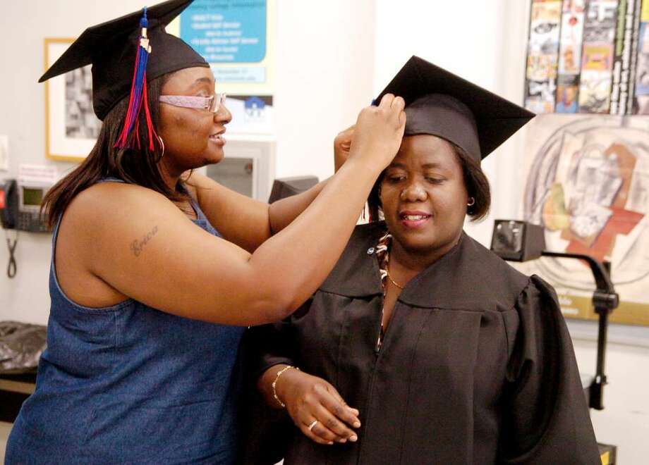 Erica Sherman helps Mimose Brice pin her cap getting ready for their graduation, both with degrees in Respiratory Care from Norwalk Community College in Norwalk, Conn. on Thursday May 20, 2010. Photo: Dru Nadler / Stamford Advocate