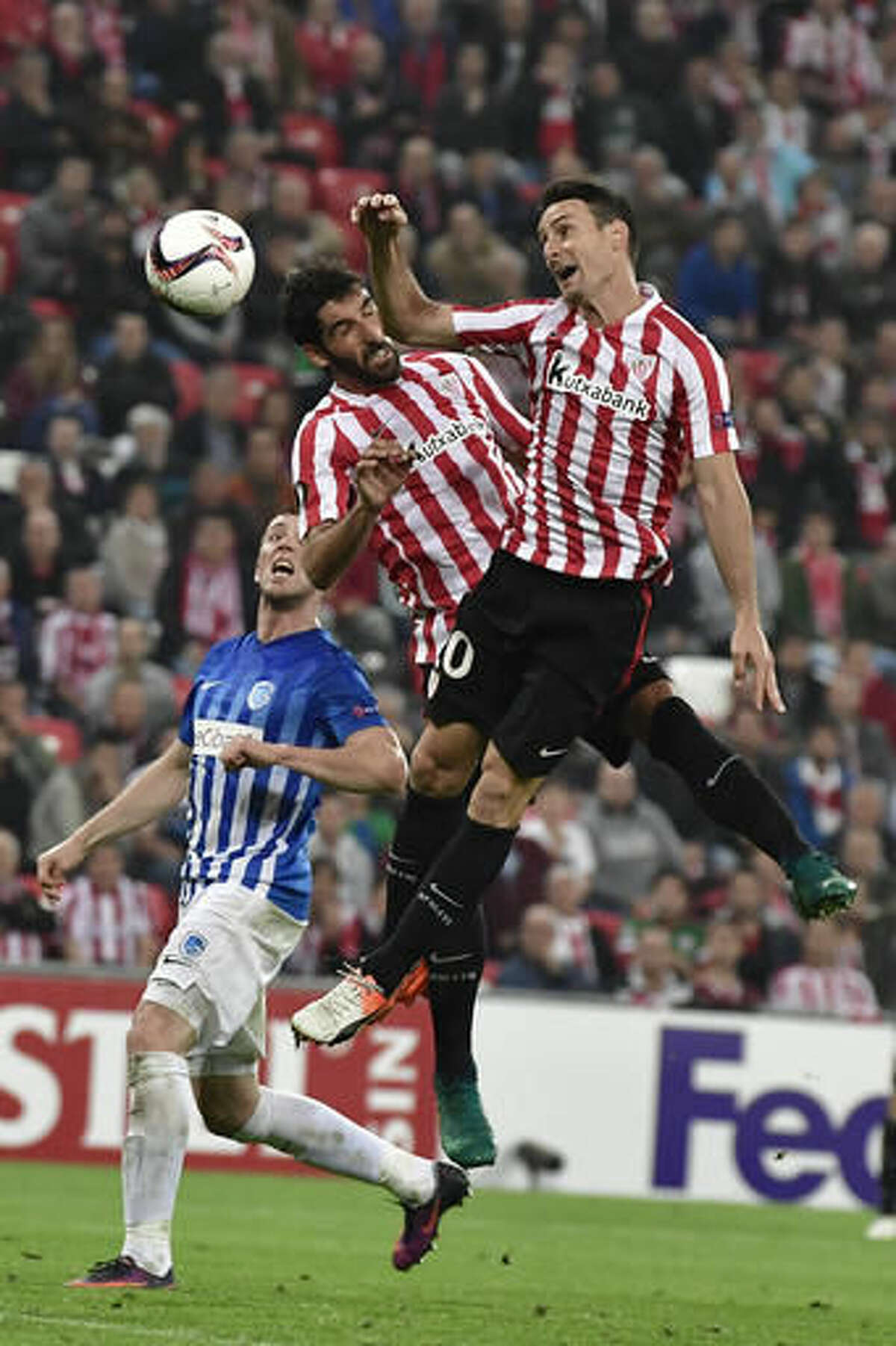 Athletic Bilbao's Aritz Aduriz, right, heads the ball beside teammate Raul Garcia, center, and Genk's Bojan Nasticto during the Europa League Group F soccer match between Athletic Bilbao and Genk, at the San Mames stadium, in Bilbao, northern Spain, Thursday, Nov. 3, 2016. (AP Photo/Alvaro Barrientos)