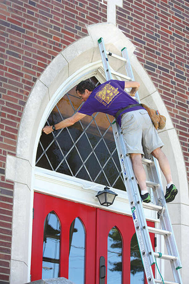 David Frei works on the window above the doors at St. Andrew's Episcopal Church.