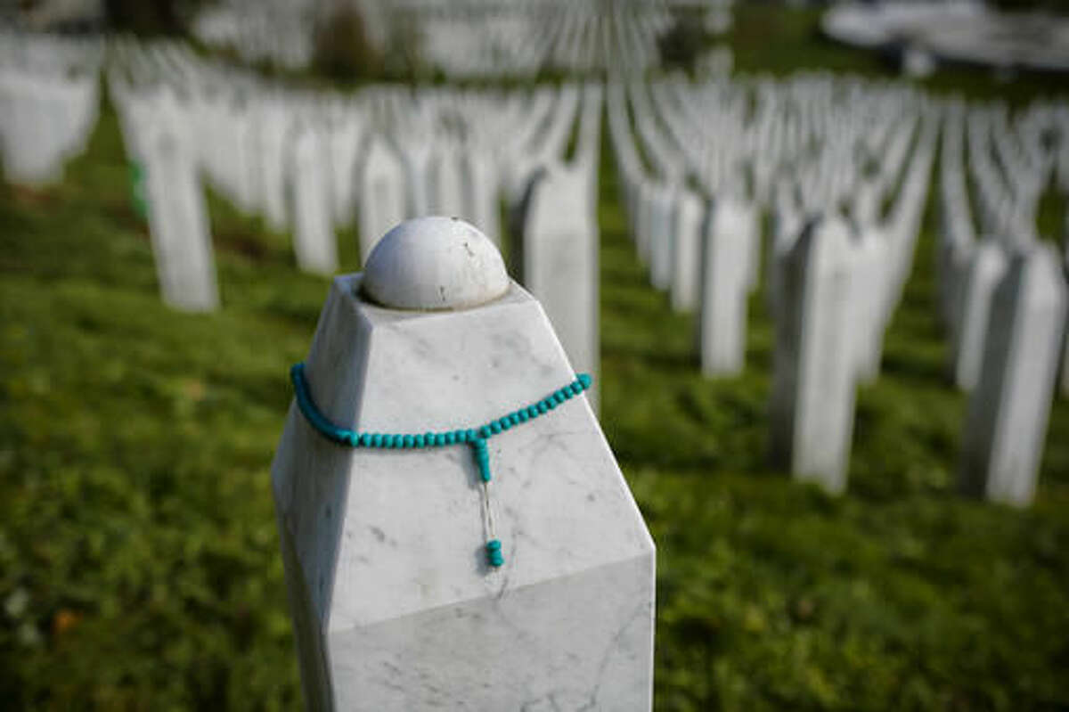 In this photo taken on Tuesday, Nov. 1, 2016, Muslim prayer beads decorate a gravestone in the memorial cemetery Potocari, of Bosnian Muslims killed during the fall of the Bosnian town of the Srebrenica massacre, near Srebrenica, 250 kms east of Sarajevo. For the first time since the Bosnian war of the 1990s, a Bosnian Serb, Mladen Grujicic, has been elected as mayor of the Bosnian town whose name is synonymous with slaughter of more than 8,000 Bosnian Muslims. (AP Photo/Amel Emric)
