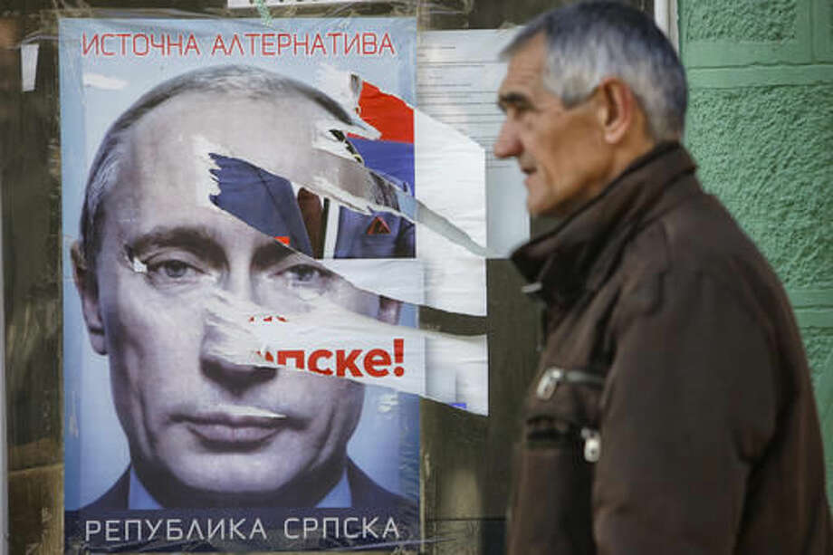 In this photo taken on Tuesday, Nov. 1, 2016, a Bosnian man passes by a poster of Vladimir Putin ahead of local elections, in the eastern Bosnian town of Srebrenica, 250 kms east of Sarajevo. For the first time since the Bosnian war of the 1990s, an ethnic Serb, Mladen Grujicic, has been elected as mayor of the Bosnian town whose name is synonymous with slaughter of more than 8,000 Bosnian Muslims. (AP Photo/Amel Emric)