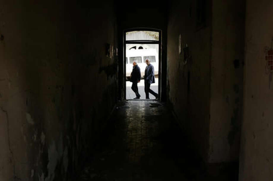 In this photo taken on Tuesday, Nov. 1, 2016, two men walk along a street in eastern Bosnian town of Srebrenica, 250 kms east of Sarajevo. For the first time since the Bosnian war of the 1990s, an Bosnian Serb, Mladen Grujicic, has been elected as mayor of the Bosnian town whose name is synonymous with slaughter of more than 8,000 Bosnian Muslims. (AP Photo/Amel Emric)