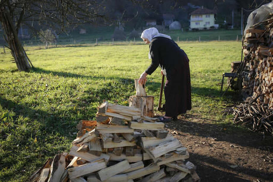 In this photo taken on Tuesday, Nov. 1, 2016, Bosnian Muslim woman Mejra Djogaz chops firewood in front of her house in the eastern Bosnian town of Srebrenica, 250 kms east of Sarajevo. For the first time since the Bosnian war of the 1990s, an ethnic Serb, Mladen Grujicic, has been elected as mayor of the Bosnian town whose name is synonymous with slaughter of more than 8,000 Bosnian Muslims. (AP Photo/Amel Emric)