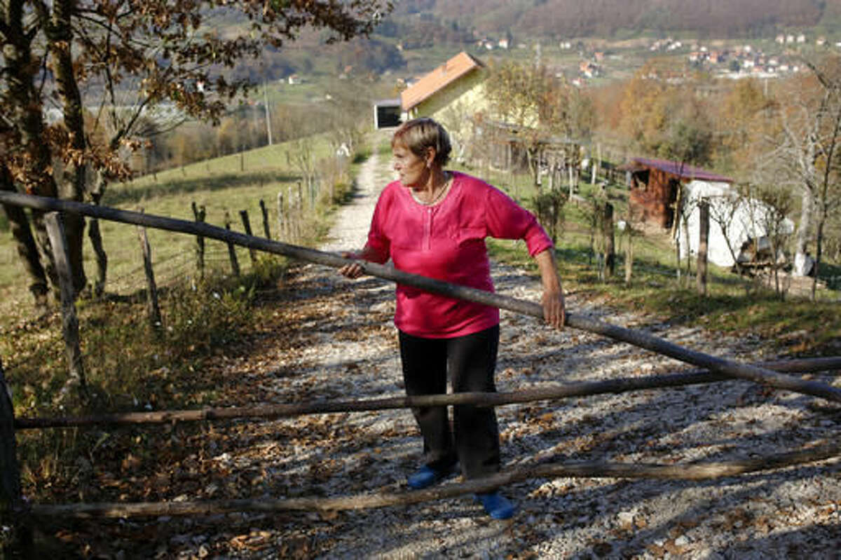 In this photo taken on Tuesday, Nov. 1, 2016 Bosnian Muslim woman Nezira Sulejmanovic opens a gate in front of her house in the eastern Bosnian town of Srebrenica, 250 kms east of Sarajevo. For the first time since the Bosnian war of the 1990s, a Bosnian Serb, Mladen Grujicic, has been elected as mayor of the Bosnian town whose name is synonymous with slaughter of more than 8,000 Bosnian Muslims. (AP Photo/Amel Emric)