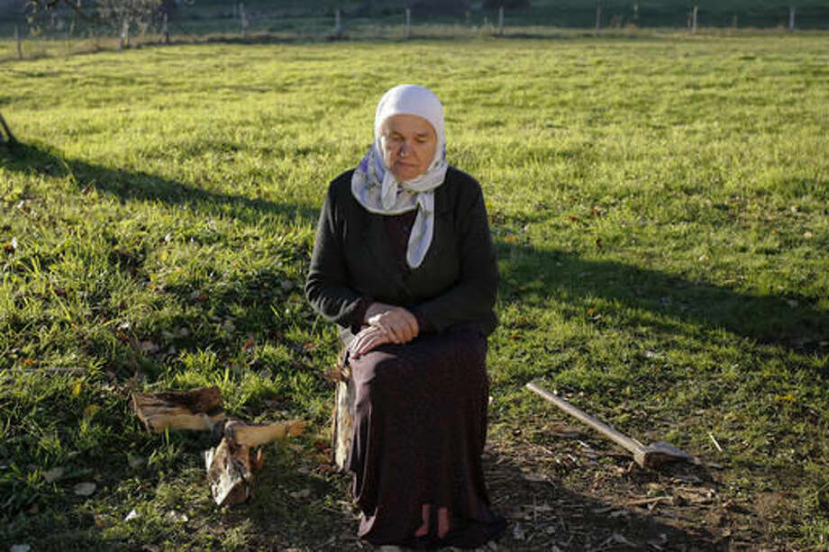 In this photo taken on Tuesday, Nov. 1, 2016, Bosnian Muslim woman Mejra Djogaz sits for a photo in front of her house in the eastern Bosnian town of Srebrenica, 250 kms east of Sarajevo. For the first time since the Bosnian war of the 1990s, an ethnic Serb, Mladen Grujicic, has been elected as mayor of the Bosnian town whose name is synonymous with slaughter of more than 8,000 Bosnian Muslims. (AP Photo/Amel Emric)