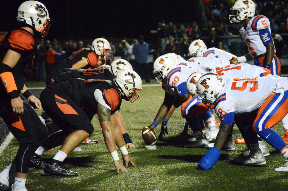 The Edwardsville defensive line, left, tries to keep the East St. Louis offense from scoring midway through the second quarter.