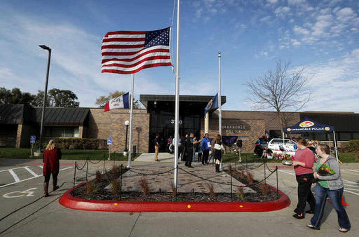 The flag flies at half-staff over the Urbandale Police Department, Wednesday, Nov. 2, 2016, in Urbandale, Iowa. Urbandale officer Justin Martin and Des Moines officer Sgt. Anthony Beminio were ambushed and fatally shot in separate attacks Wednesday as they sat in their patrol cars, authorities said. (AP Photo/Charlie Neibergall)