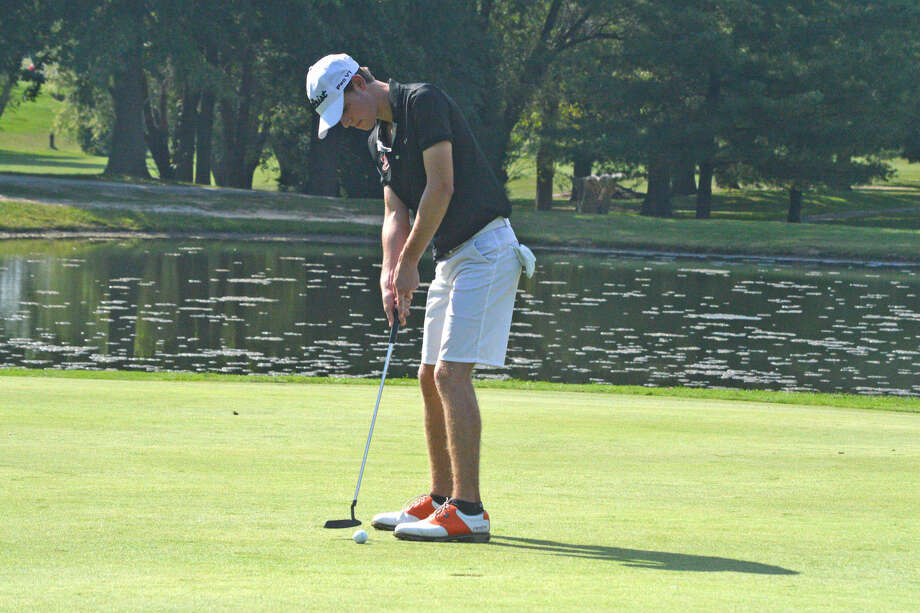 Edwardsville's Tanner White hits a putt towards the hole.
