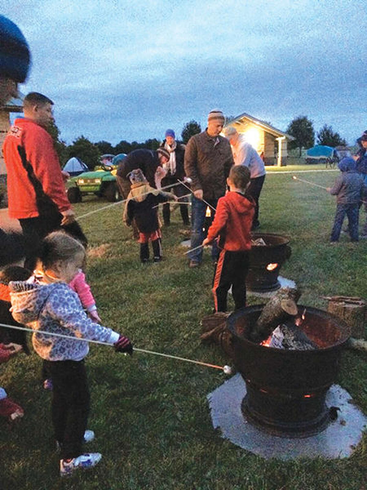 Participants in a previous Family Camp Out at Glik Park toast marshmallows over a fire pit as they make s'mores.