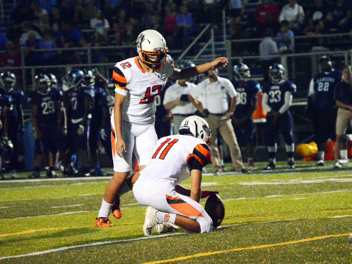 Edwardsville kicker Devin Parker hits one of his seven extra points on Friday with Blake Neville as the holder.