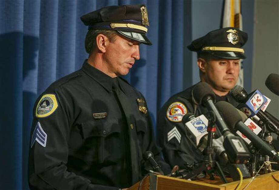 Des Moines Police Sgt. Paul Parizek, left, pauses to fights back emotions as he speaks to media during a press conference on Thursday, Nov. 3, 2016, at the Des Moines Police Department in Des Moines, Iowa, regarding the fatal shooting of two officers. Police say 46-year-old Scott Michael Greene was taken into custody Wednesday hours after the killings when he turned himself in to an Iowa Department of Natural Resources employee west of Des Moines. (Bryon Houlgrave/The Des Moines Register via AP)
