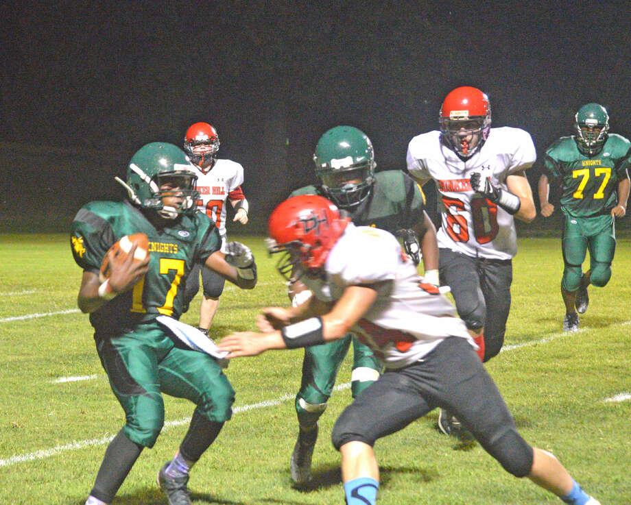 MELHS junior quarterback Damion Brooks tries to get past a Bunker Hill defender.