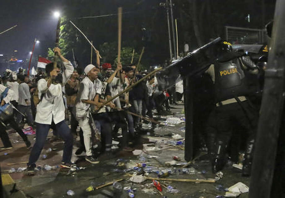 Protesters use sticks to attack riot police during a clash outside the presidential palace in Jakarta, Indonesia, Friday, Nov. 4, 2016. Police in the Indonesian capital clashed with hard-line Muslim protesters refusing to disperse after a massive protest Friday to demand the arrest of the city's minority-Christian governor for alleged blasphemy. (AP Photo/Tatan Syuflana)