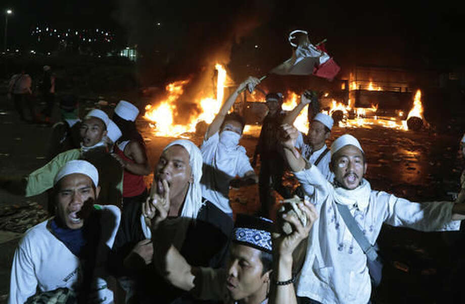 Muslim protesters chant slogans near burning police trucks during a clash with the police outside the presidential palace in Jakarta, Indonesia, Friday, Nov. 4, 2016. Police in the Indonesian capital clashed with hard-line Muslim protesters refusing to disperse after a massive protest Friday to demand the arrest of the city's minority-Christian governor for alleged blasphemy. (AP Photo/Dita Alangkara)