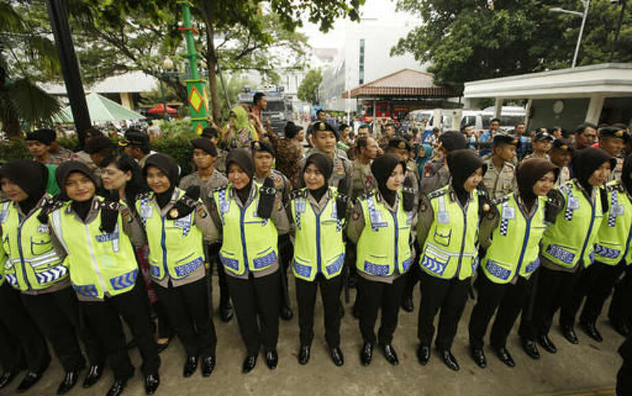 Indonesian Muslim police women guard during a protest outside of the City Hall. Friday, Nov. 4, 2016. Thousands of hard-line Muslims converged Friday on the center of the Indonesian capital to demand the arrest of its governor for alleged blasphemy. (AP Photo/Achmad Ibrahim)