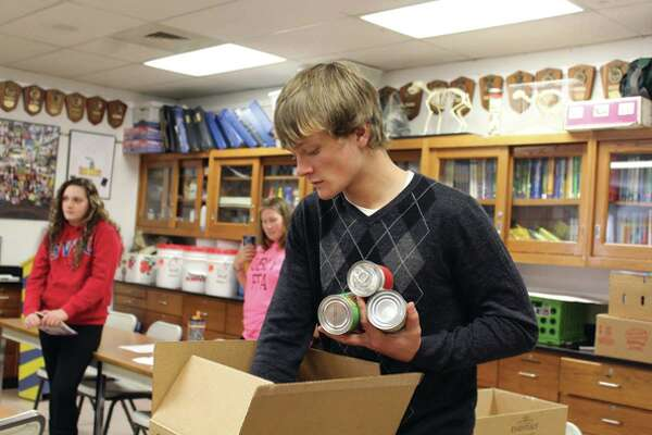 Skyler Lesoski packs food into boxes. Ubly FFA members collected food each day from classes in the building. They weighed and packaged all the food, which was donated to the local food pantry.