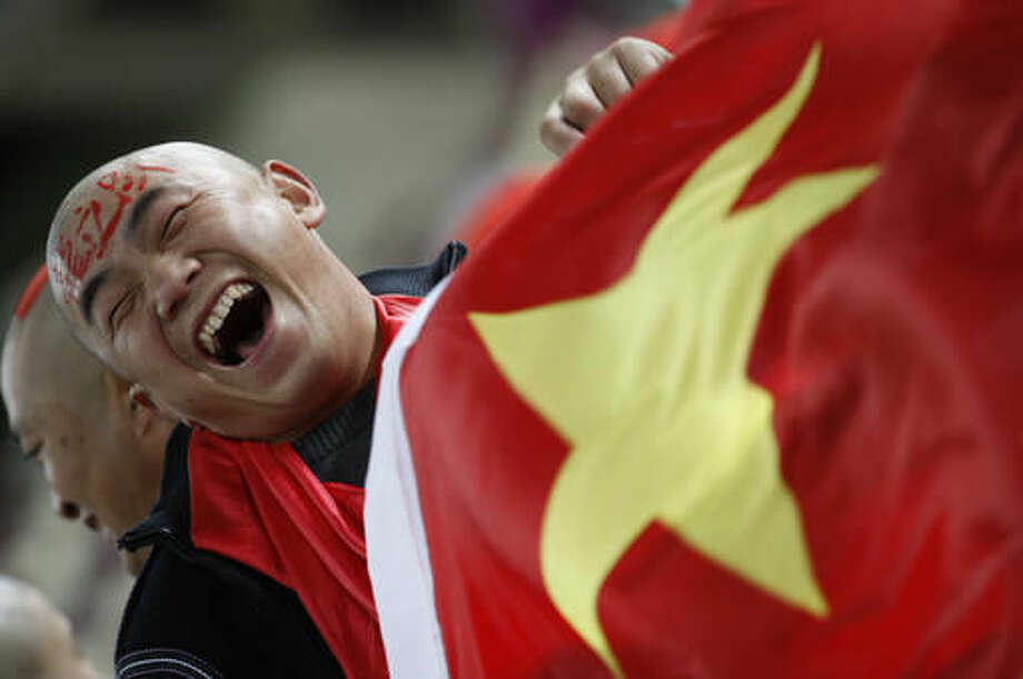 FILE - In this Wednesday, Jan. 12, 2011, file photo, a Chinese soccer fan cheers for his team before their AFC Asian Cup group A soccer match against Qatar in Doha, Qatar. Ever since the Chinese Football Association announced it had coaxed Lippi out of retirement, the nation's long-suffering fans have responded with more than a hint of skepticism. Given the team's record of failure under a string of foreign and Chinese coaches, the problems are more often attributed to the lack of a strong youth program and a misplaced, money-driven focus on the domestic league. (AP Photo/Hassan Ammar, File)
