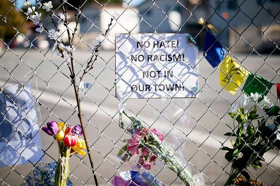 Flowers and a sign hang at a makeshift memorial for murder victim William Sims on Thursday, Dec. 1, 2016, in El Sobrante, Calif. Investigators said Sims, a 28-year-old African American musician, was targeted because of his race.