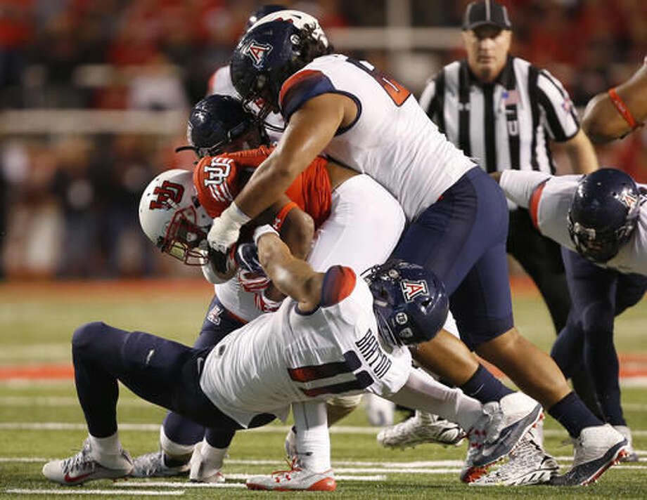 Utah running back Armand Shyne (23) is tackled by Arizona linebacker Michael Barton (11) and defensive lineman Aiulua Fanene (62) during the first half of an NCAA college football game, Saturday, Oct. 8, 2016, in Salt Lake City. (AP Photo/George Frey)