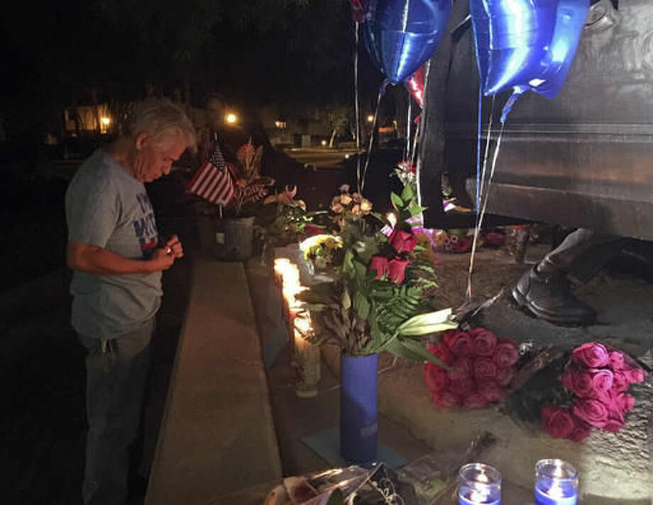 A citizen lights candles at a memorial for two slain police officers in Palm Springs, Calif., on Saturday, Oct. 8, 2016. Police Chief Bryan Reyes says three officers in Palm Springs, California were trying to resolve a family dispute Saturday when a man fatally shot two of them and wounded the third. (AP Photo/Robert Jablon)