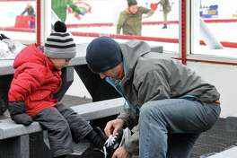 Paul Fekete of Clifton Park puts skates on his son Weston Fekete, 3, at the Empire State Plaza ice rink on Friday Feb. 5, 2016 in Albany, N.Y.  (Michael P. Farrell/Times Union)