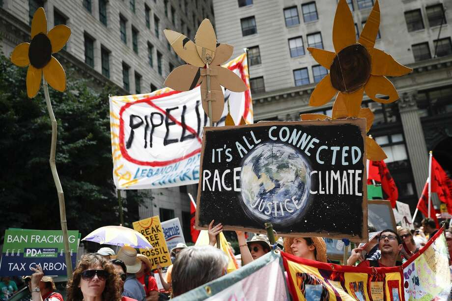 "In this Sunday, July 24, 2016 file photo, climate change activists carry signs as they march during a protest in downtown in Philadelphia a day before the start of the Democratic National Convention. Matthew Nisbet, a communications professor at Northeastern University, says the split with science is most visible and strident when it comes to climate change because the nature of the global problem requires communal joint action, and ""for conservatives that's especially difficult to accept."" He and other experts say climate change is more about tribalism, or who we identify with politically and socially. Liberals believe in global warming, conservatives don't. (AP Photo/John Minchillo) Photo: John Minchillo/Associated Press"