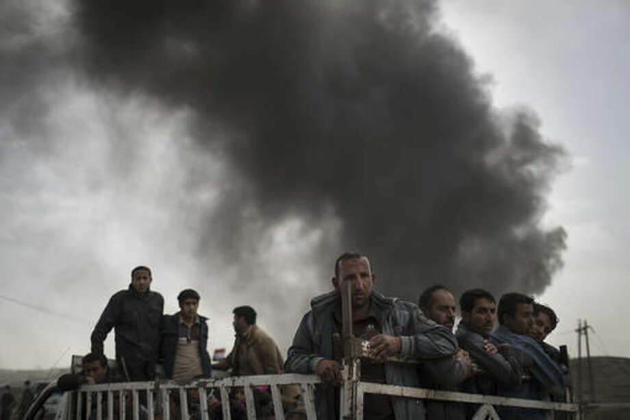 Displaced people stand on the back of a truck at a checkpoint near Qayara, south of Mosul, Iraq, Tuesday, Nov. 1, 2016. The U.N. human rights office is lauding efforts by the U.S.-led coalition in the battle against the Islamic State group in Mosul. The office in Geneva says coalition flights over Iraq have largely succeeded in preventing IS from bringing in 25,000 more civilians to the city center, where the militant group has been using people as human shields as Iraqi forces advance on Mosul. (AP Photo/Felipe Dana)