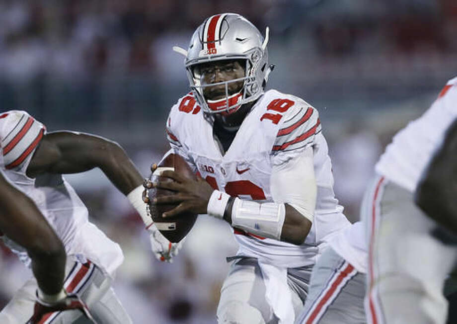 "FILE - In this Saturday, Sept. 17, 2016, file photo, Ohio State quarterback J.T. Barrett (16) scrambles during the fourth quarter of an NCAA college football game against Oklahoma in Norman, Okla. After blowing away opponents in the first four games, Ohio State's plummet back to earth has included offensive woes, an upset by unranked Penn State and a narrow escape against three-touchdown underdog Northwestern at home. Coach Urban Meyer has taken to calling the team a ""project"" still in the works, as if to reset expectations that soared in the first month of the season when quarterback Barrett was breaking school passing records and new ball-hawking stars were emerging on the defense. (AP Photo/Sue Ogrocki, File)"