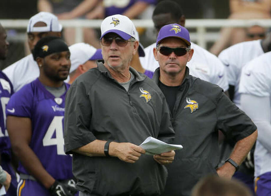 FILE - In this July 27, 2015, file photo, Minnesota Vikings offensive coordinator Norv Turner, left, and head coach Mike Zimmer watch practice at an NFL football training camp on the campus of Minnesota State University, in Mankato, Minn. Vikings offensive coordinator Norv Turner has resigned. He's been replaced on an interim basis by Pat Shurmur. The Vikings announced the news on Wednesday, Nov. 2, 2016, two days after their second consecutive defeat. (AP Photo/Charles Rex Arbogast, File)
