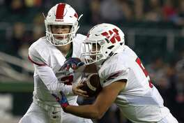 The Woodlands quarterback Eric Schmid (3) hands the ball off to running back Carlos Ramos (5) during the third quarter of a Class 6A Division I regional semifinal game at McLane Stadium Saturday, Nov. 26, 2016, in Waco. The Woodlands defeated Austin Bowie 52-31.