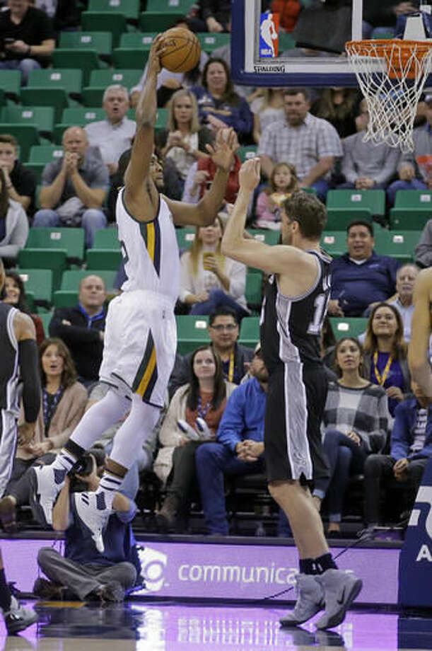 Utah Jazz forward Derrick Favors, left, goes up for a dunk against San Antonio Spurs center Pau Gasol during the first quarter during an NBA basketball game Friday, Nov. 4, 2016, in Salt Lake City. (AP Photo/Rick Bowmer)